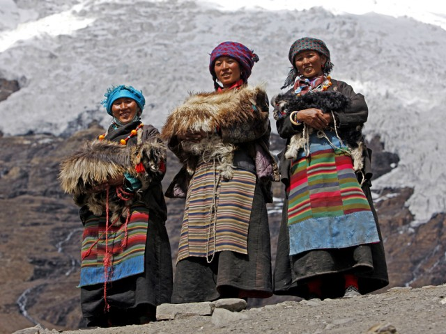 Three Tibetan women in traditional dresses